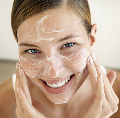 Smiling Young Woman Applying Face Cream --- Image by © Royalty-Free/Corbis